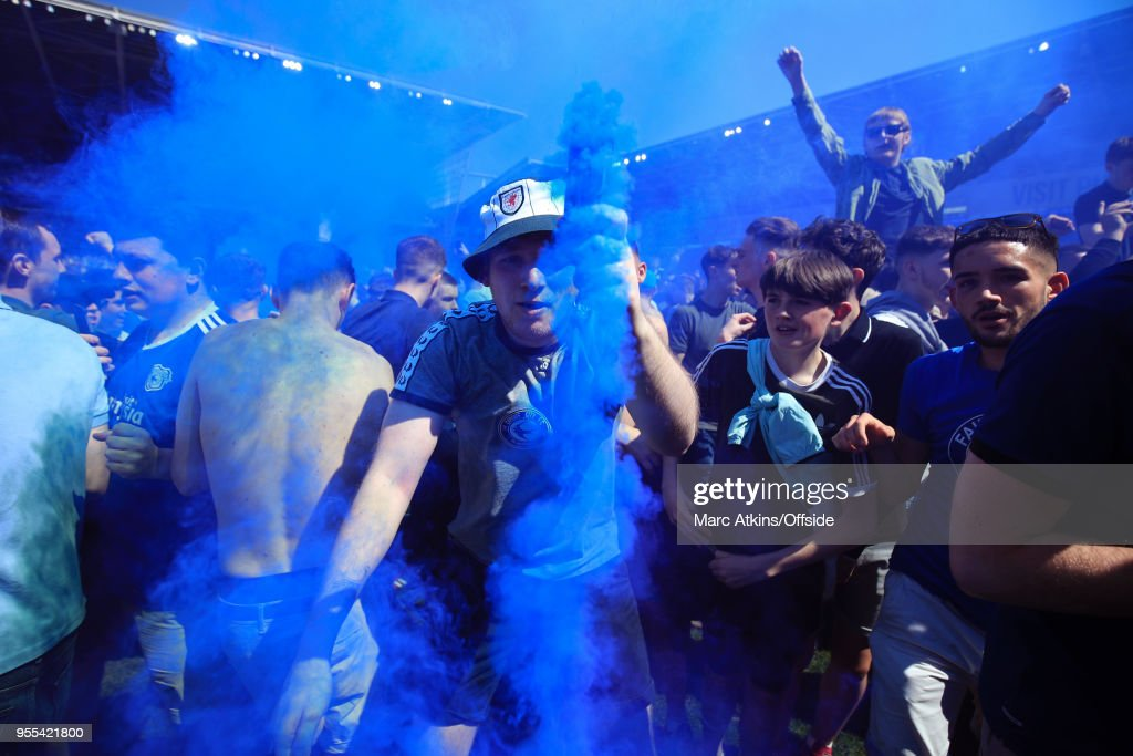 A Cardiff City fan dances in celebration with a smoke bomb during the Sky Bet Championship match between Cardiff City and Reading at Cardiff City Stadium on May 6, 2018 in Cardiff, Wales.