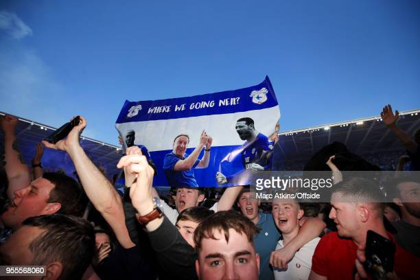 Cardiff City fans celebrate on the pitch after promotion holding a banner featuring Cardiff City manager Neil Warnock during the Sky Bet Championship...