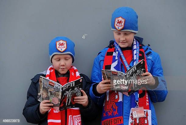 Cardiff City fans read matchday programmes prior to the Barclays Premier League match between Cardiff City and West Bromwich Albion at Cardiff City...
