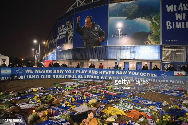 Cardiff City fans unveil a flag in front of tributes for their £15 Million forward Emiliano Sala after the search for the missing Footballer and...