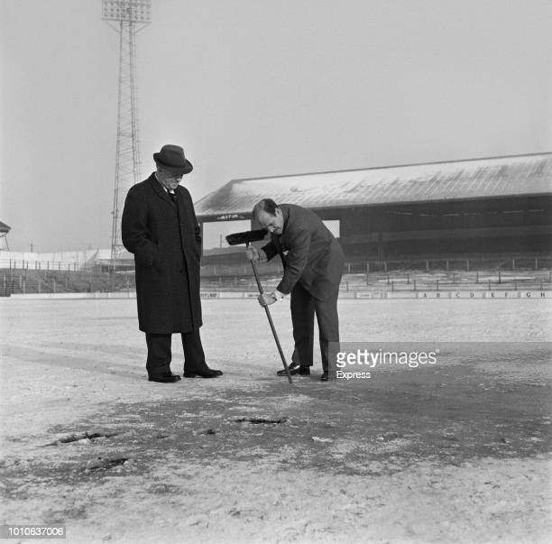 Cardiff City FC Chairman Fred Dewey looks on as manager Jimmy Scoular uses a broom to demonstrate the state of the frozen pitch at Ninian Park...