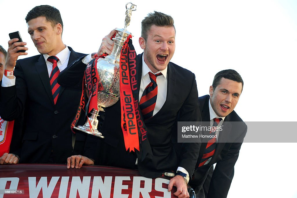 Cardiff City FC players (L-R) Mark Hudson, Aron Gunnarsson and Don Cowie celebrate with the trophy as they ride in an open top bus through the city centre during a victory parade in honour of the football club winning the npower Championship League trophy on May 05, 2013 in Cardiff, Wales.