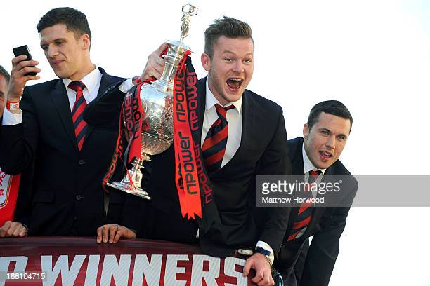 Cardiff City FC players Mark Hudson Aron Gunnarsson and Don Cowie celebrate with the trophy as they ride in an open top bus through the city centre...