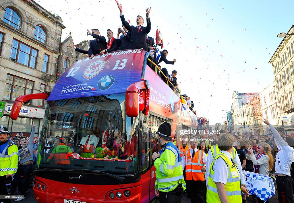 Cardiff City FC players ride in an open top bus through the city centre during a victory parade in honour of the football club winning the npower Championship League trophy on May 05, 2013 in Cardiff, Wales.
