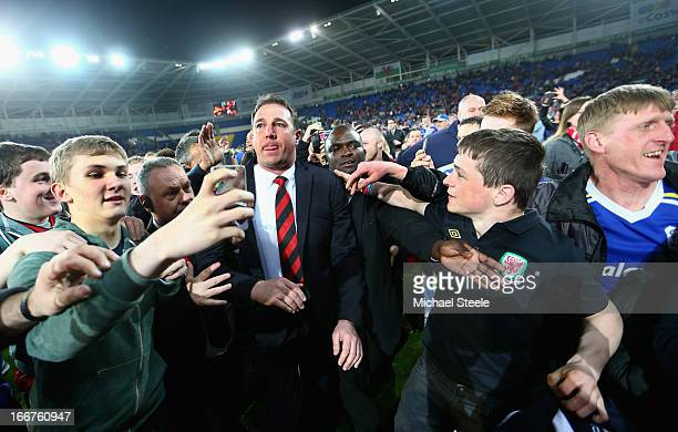Cardiff City Manager Malky Mackay is mobbed by fans after his team's promotion to the Premier League at the end of the npower Championship match...