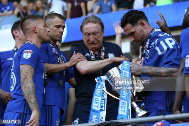 Cardiff City manager Neil Warnock stumbles as he reaches for the trophy during the Sky Bet Championship match between Cardiff City and Reading at...