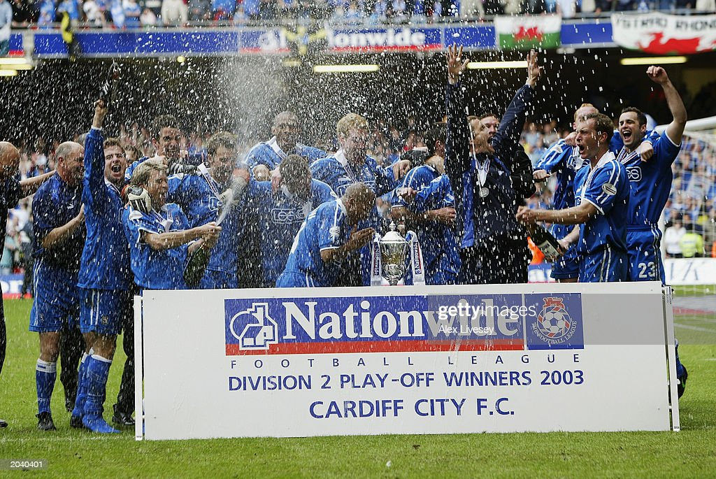 Cardiff City players celebrate promotion with the trophy and champagne : News Photo