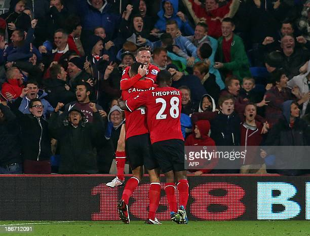 Cardiff City's English defender Steven Caulker is congratulated by teammates, Cardiff City's Welsh striker Craig Bellamy and Cardiff City's French...