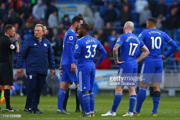 Cardiff City's English manager Neil Warnock and his players react to their defeat on the pitch after the English Premier League football match...
