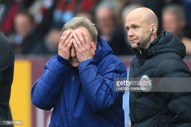 Cardiff City's English manager Neil Warnock reacts on the touchline as fourth official Anthony Taylor looks on during the English Premier League...