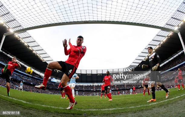 Cardiff City's Kevin McNaughton fails to clear a shot from Manchester City's Edin Dzeko who scores their 100th goal of the season during the Barclays...