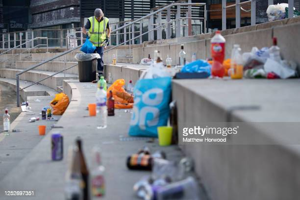 Cardiff Council worker clears up bottles and rubbish left behind at Roald Dahl Plass after a late-night lockdown party on June 26, 2020 in Cardiff,...