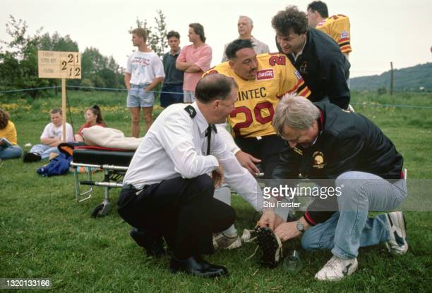 Cardiff Mets cornerback Andy Pellatt receives treatment for an injury from a member of the St John's Ambulance and chairman Paul Evans during a Coca...