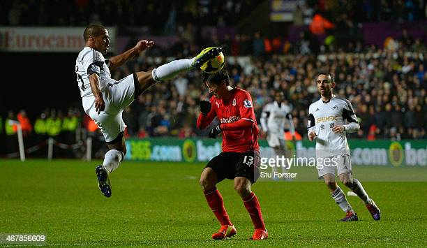 Cardiff player Kim Bo Kyung is challenged by Wayne Routledge during the Barclays Premier League match between Swansea City and Cardiff City at...