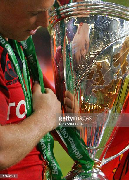 Man of the match Peter Stringer of the Irish team Munster is reflected in the Heineken Cup European final trophy at the Millennium Stadium in Cardiff...