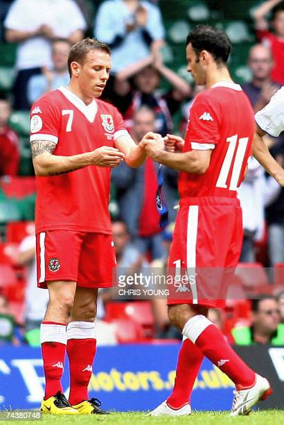 Cardiff, UNITED KINGDOM: Wales Ryan Giggs hands the captain's armband to Craig Bellamy as he is substituted and retires from international football...