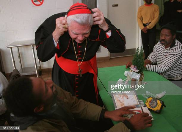 Cardinal Bernard Law checks out some music with the help of Mike's headphones and tape deck during a Christmas Eve visit to the Pine Street Inn in...