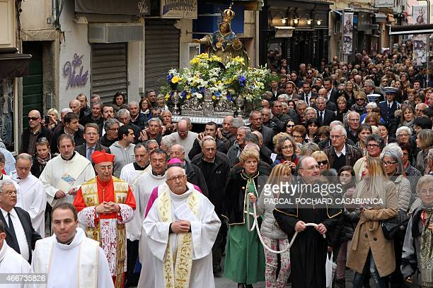 Cardinal Dominique Mamberti and Corsican bishop Olivier de Germay walk in the Madunuccia sacred procession on March 18 2015 in Ajaccio on the French...
