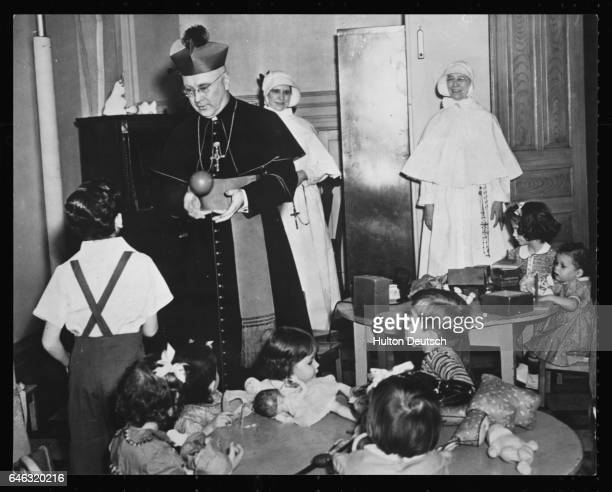 Cardinal Francis Spellman archbishop of New York plays catch with an Orphan at the New York Foundling Hospital