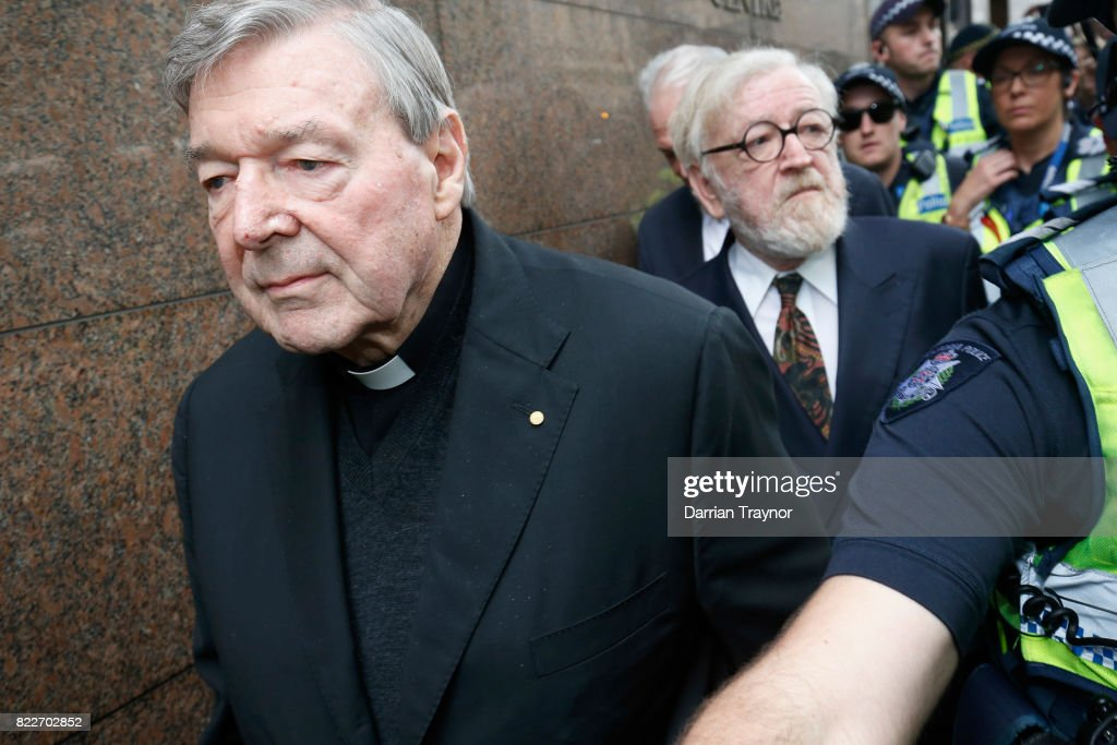 Cardinal George Pell and his barrister Robert Richter leave the Melbourne Magistrates Court with a heavy police guard in Melbourne on July 26, 2017 in Melbourne, Australia. Cardinal Pell was charged on summons by Victoria Police on 29 June over multiple allegations of sexual assault. Cardinal Pell is Australia's highest ranking Catholic and the third most senior Catholic at the Vatican, where he was responsible for the church's finances. Cardinal Pell has leave from his Vatican position while he defends the charges.