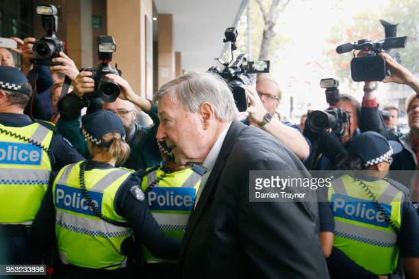 Cardinal George Pell walks through a police guard at Melbourne Magistrates' Court on May 1 2018 in Melbourne Australia Cardinal Pell was charged on...