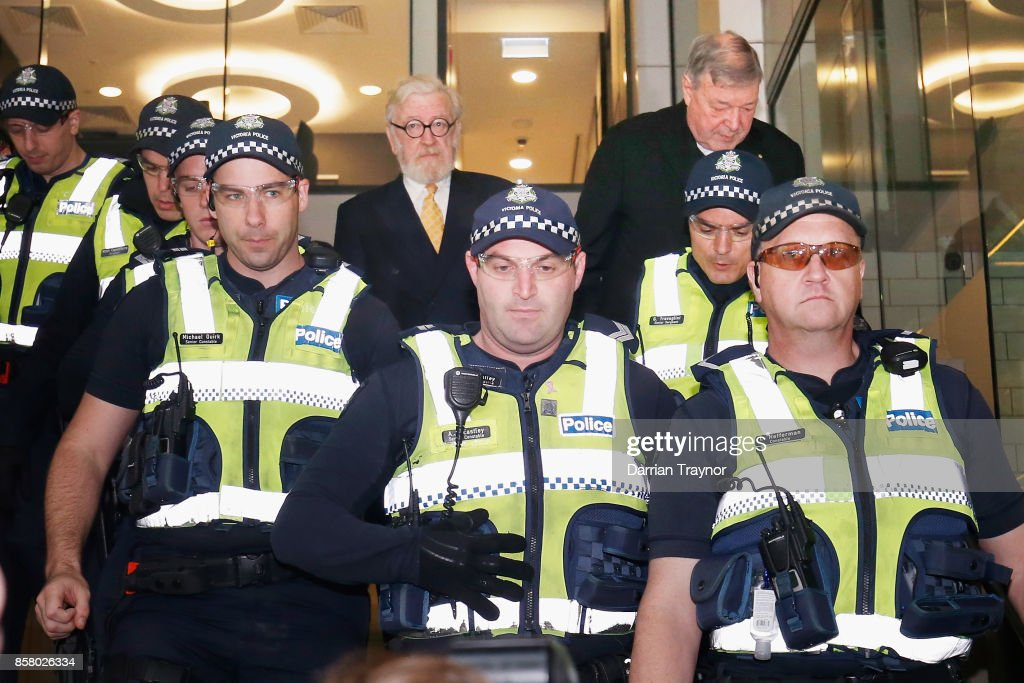 Cardinal George Pell walks with a heavy Police escort from his lawyers office to the Melbourne Magistrates' Court on October 6, 2017 in Melbourne, Australia. Cardinal Pell was charged on summons by Victoria Police on 29 June over multiple allegations of sexual assault. Cardinal Pell is Australia's highest ranking Catholic and the third most senior Catholic at the Vatican, where he was responsible for the church's finances. Cardinal Pell has leave from his Vatican position while he defends the charges.