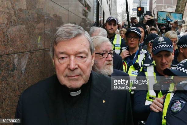 Cardinal George Pell walks with a heavy Police guard from the Melbourne Magistrates' Court on July 26 2017 in Melbourne Australia Cardinal Pell was...
