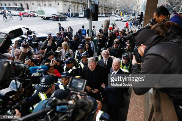 Cardinal George Pell walks with a heavy Police guard to the Melbourne Magistrates' Court on July 26 2017 in Melbourne Australia Cardinal Pell was...