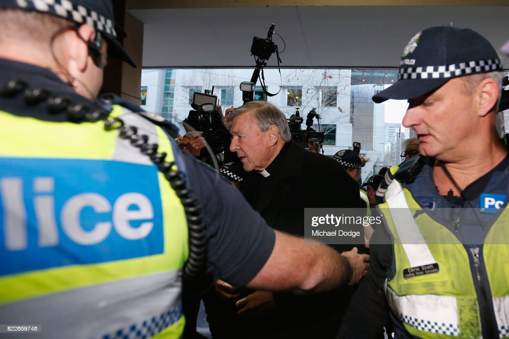 Cardinal George Pell walks with a heavy Police guard to the Melbourne Magistrates' Court on July 26, 2017 in Melbourne, Australia. Cardinal Pell was charged on summons by Victoria Police at Melbourne Magistrates' Court on July 26, 2017 in Melbourne, Australia. Cardinal George Pell was charged on summons by Victoria Police on 29 June over multiple allegations of sexual assault. Cardinal George Pell is Australia's highest ranking Catholic and the third most senior Catholic at the Vatican, where he was responsible for the church's finances. Cardinal George Pell has leave from his Vatican position while he defends the charges.