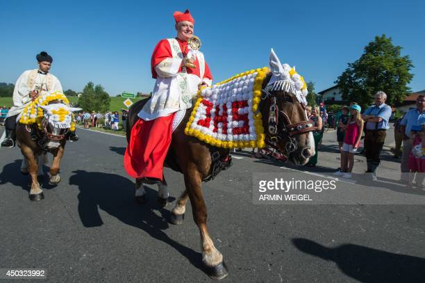Cardinal Gerhard Ludwig Mueller participates in the Pentecostal horse ride parade on June 9 2014 near Bad Koetzting Germany The procession with...