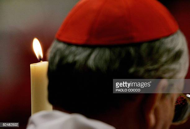 Cardinal holds a candle during a candle-lit vigil in St. Peter's Basilica presided by German Cardinal Joseph Ratzinger 26 March 2005. Though he was...