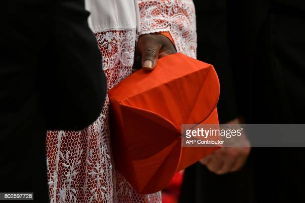 A cardinal holds his red threecornered biretta hat before the start of a consistory for the creation of five new cardinals on June 28 2017 at St...