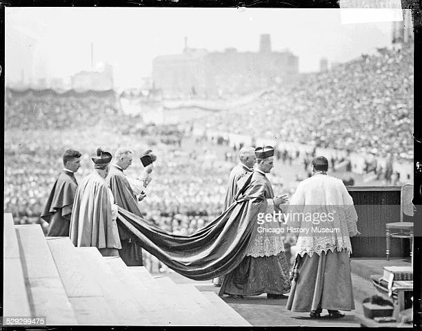 Cardinal John Bonzano and clergymen walking atop a high platform in Soldier Field during the International Eucharist Congress Chicago Illinois 1926