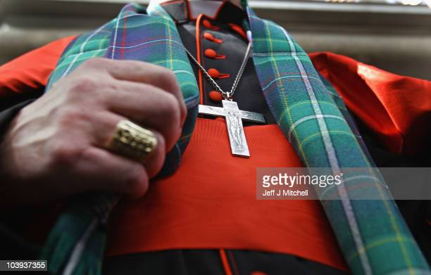 Cardinal Keith Patrick O'Brien unveils the world's first ever Papal visit tartan outside the Scottish Parliament before handing it over to...
