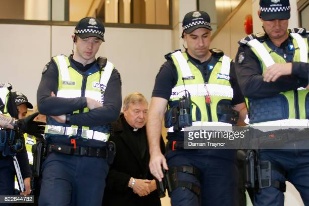 Cardinal Pell walks with a heavy Police guard from his barristers Robert Richter office to the Melbourne Magistrates' Court on July 26 2017 in...