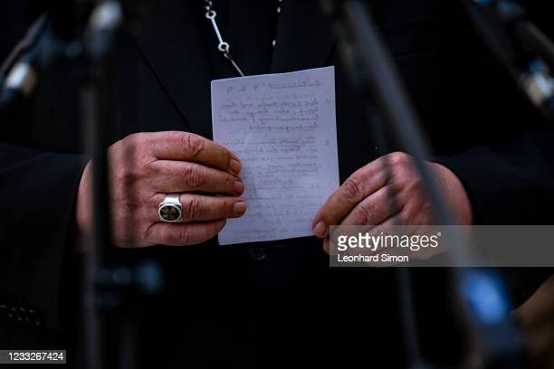Cardinal Reinhard Marx, the Catholic Archbishop of Munich and Freising, holds notes in his hands and speaks to the media following his offer of...