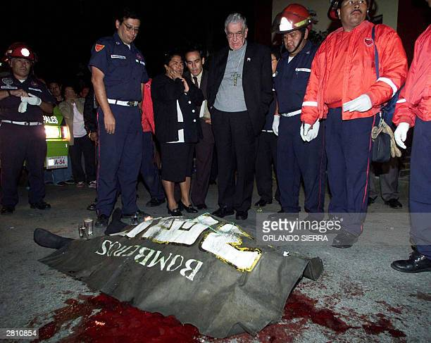 Cardinal Rodolfo Quezada Toruno looks at the body of killed priest Father Jose Maria Ruiz lying on the pavement in Guatemala City 14 December 2003...