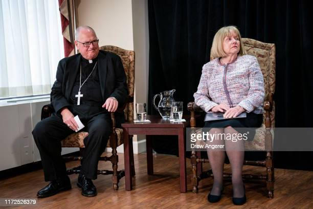Cardinal Timothy Dolan, Archbishop of New York, and former federal judge Barbara Jones take their seats at the start of a news conference regarding...