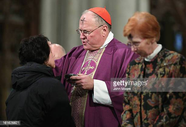 Cardinal Timothy Dolan, Archbishop of New York, marks a woman's forehead with ashes while celebrating Ash Wednesday with fellow Catholics at St....