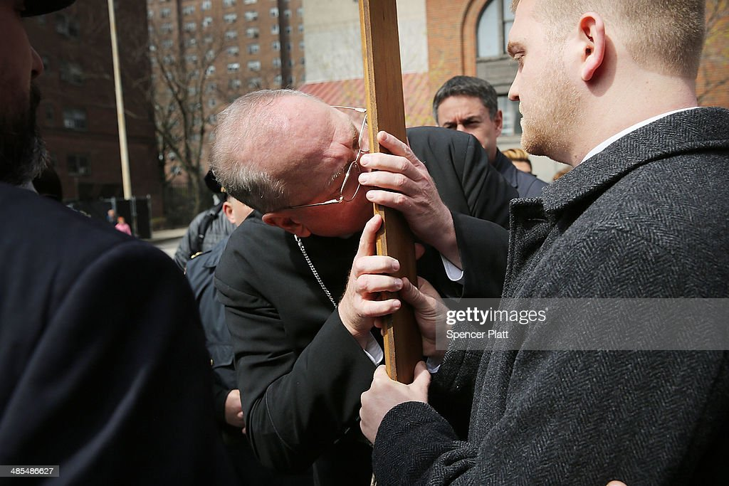 Cardinal Timothy Dolan kisses the cross during the start of the Way of the Cross procession over the Brooklyn Bridge on April 18, 2014 in the Brooklyn borough of New York City. The Way of the Cross is a traditional Catholic procession recalling the suffering and death of Jesus Christ and often includes Gospel readings, choral music and readings at stations along the way. This is 19th anniversary of the procession across the iconic bridge.