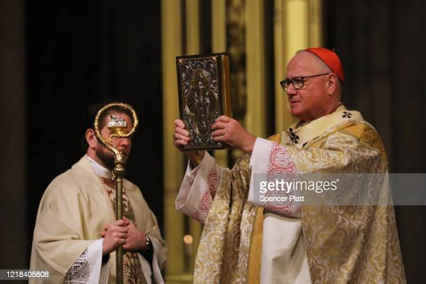 Cardinal Timothy Dolan, the Archbishop of New York, celebrates Easter Sunday Mass in a nearly empty St. Patrick's Cathedral as the cornovirus...