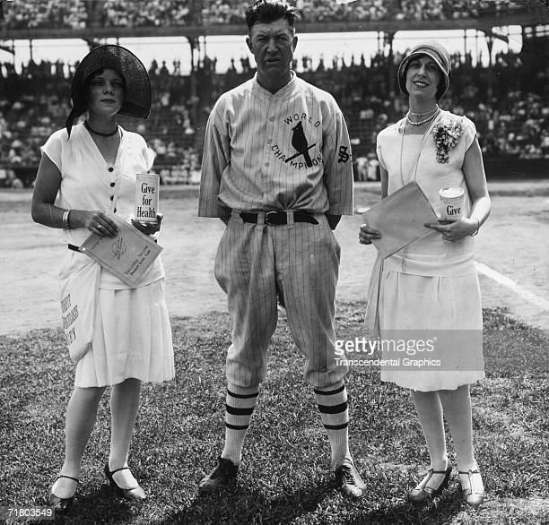Cardinals pitcher Grover Cleveland Alexander poses before a game in Sportsmans Park in St Louis flanked by two flappers promoting a health charity
