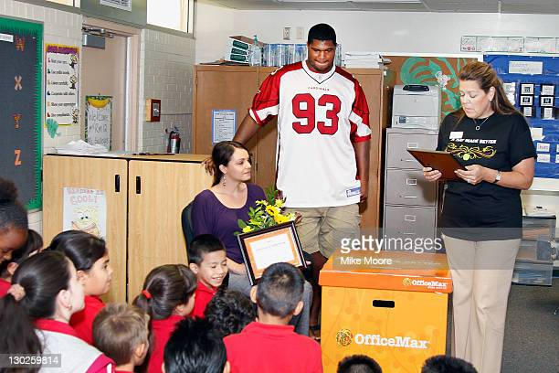 Cardinals Player Calais Campbel looks on as Office Max team member Kelli Roy reads a poem to winning teacher Andrea Gallegos during the Office Max A...