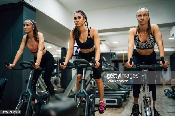 cardio workout in a gym - spinning stock pictures, royalty-free photos & images