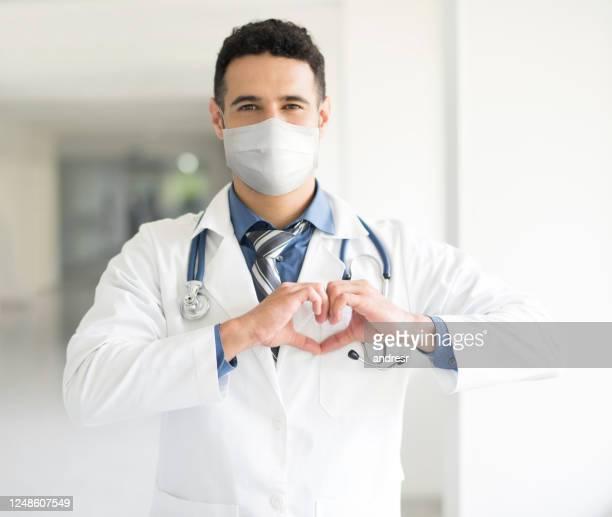 cardiologo che lavora in ospedale durante la pandemia di covid-19 indossando una maschera facciale - cardiologo foto e immagini stock