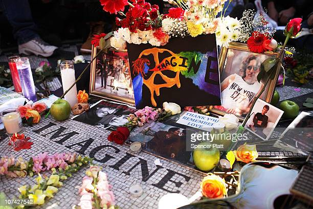 Cards candles and pictures placed there by hundreds of fans adorn a memorial at Strawberry Fields in Central Park on the 30th anniversary of the...