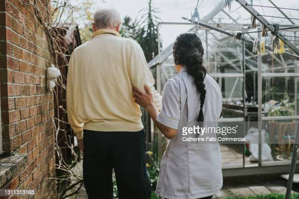 a care assistant physically supports an elderly male while they walk in a garden - serving sport stock pictures, royalty-free photos & images