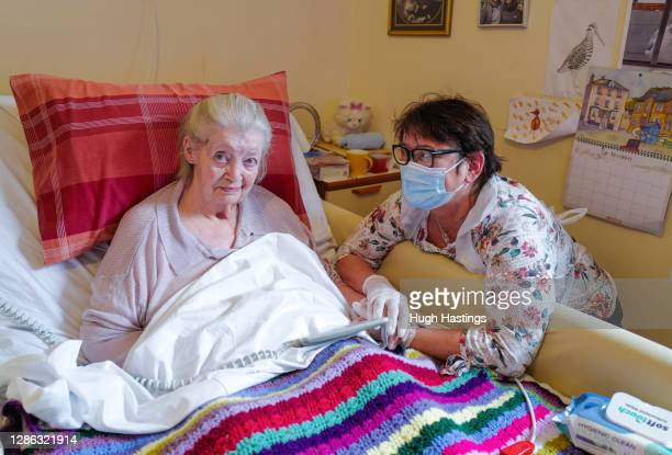 Care home resident Dot Hendy holds her daughter Louise's hand for the first time since March after Louise successfully passed a Rapid Covid-19 Test...
