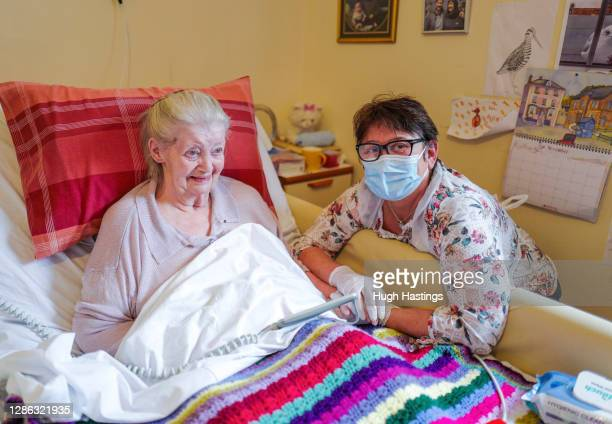 Care home resident Dot Hendy holds her daughter Louise's hand for the first time in since March after Louise successfully passed a Rapid Covid-19...