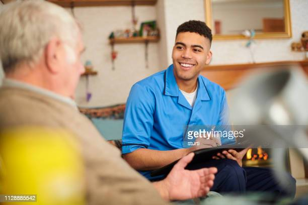 care nurse checking patient at home - healthcare worker stock pictures, royalty-free photos & images